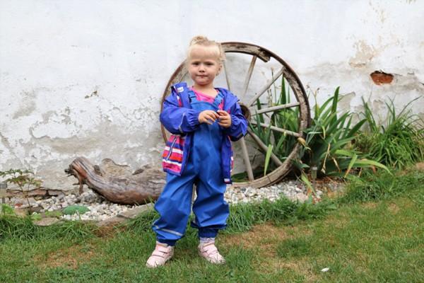 holčička oblečená do modrých nepromokavých kalhot a bundy z Lidlu (Lupilu)
