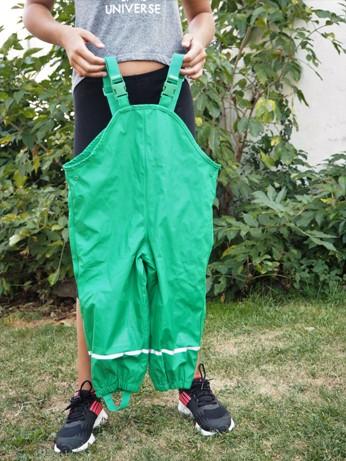 dívka drží nepromokavé kalhoty pro děti značky Lupilu