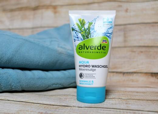 čistící pleťový gel Alverde leží na dřevěné desce spolu s modrým ručníkem