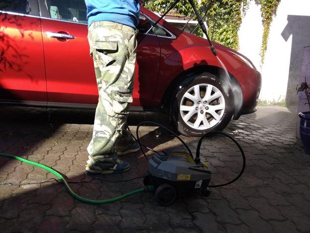 muž wapkuje kola aut pomocí vysokotlakého čističe Parkside z Lidlu