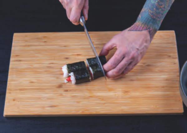 kuchař na dřevěné podložce nožem krájí sushi rolky
