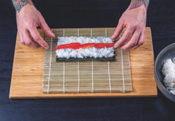 Na sushi rýži leží zelenina