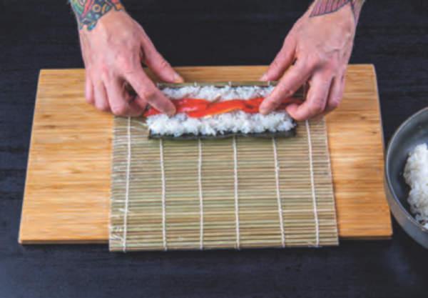 kuchař ukazuje postup rolování mořské řasy na sushi rýži